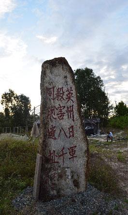 陵水黎族自治県英州鎮にある日本軍によって殺害された八千人の碑。後ろの死体が入れられた穴は、草に覆われている(二〇一五年一一月二一日)